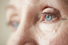 Sad eyes of elderly woman. Sad blue-grey eyes of elderly woman looking to the side, extreme close-up shot royalty free stock photo