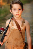 Sad Eyes Fishing. A 7 year old young boy in overalls, with sad eyes going fishing with his pole and fishing basket. Shallow depth of field Royalty Free Stock Photo