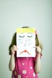 Sad face. Little blonde girls holding sad face mask royalty free stock photo