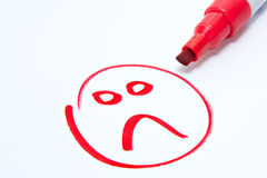Sad face. Drawn on white with red pen showing customer dissatisfaction royalty free stock photography