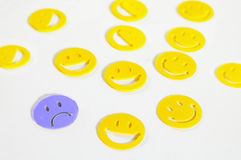 Sad face. Assorted yellow smiley faces with one blue frown Stock Images