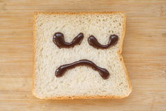 Sad face. Applied to the surface of the bread on the sad face Stock Photography