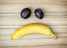 Sad face of banana and plums, emotions, fruit theme Royalty Free Stock Photography
