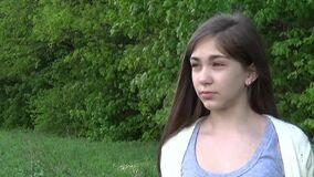 Sad face beautiful young girl looking away outdoors in the park, close-up portrait of serious teenager. Sad face beautiful young girl looking away outdoors stock footage
