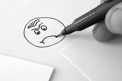 Sad face drawing. Hand and pen drawing a sad face on paper Stock Photography