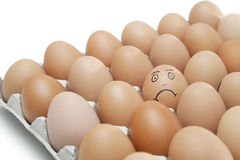 Sad face drawn on an egg surrounded by plain brown eggs in carton against white background Stock Photo