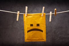 Sad face emoticon on mail Envelope. Sad face emoticon on Postal mail Envelope hanging on rope attached with clothes pins. Bad news concept Stock Photo