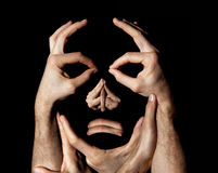 Sad face made with hands. Black background. Sad face made with hands. An unhappy face made with human hands. Concept of construction and manipulation of mood stock photo