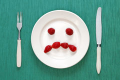 Sad face made of strawberries Stock Photos