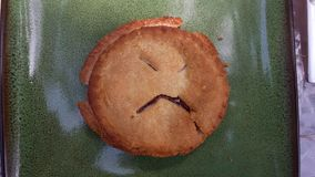 Sad face in mini cherry pie on a green plate. Mini cherry pie square Royalty Free Stock Image