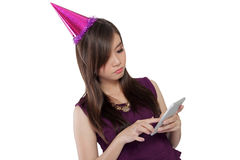 Sad face of party girl using smartphone, on white. Pretty Asian girl in party costume looking at her smartphone screen with sad face, isolated on white Stock Photography