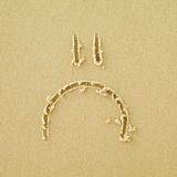 Sad face sign on a sand Stock Photos