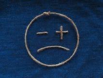 Sad face of twine in denim. Emoji. Sign handmade icon stock photos