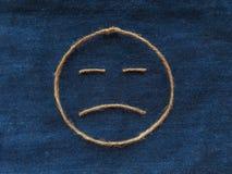 Sad face of twine in denim. Emoji sign handmade icon.  royalty free stock image