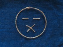 Sad face of twine in denim. Emoji sign handmade icon.  royalty free stock photography