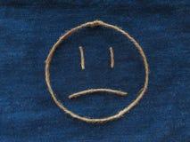 Sad face of twine in denim. Emoji sign handmade icon.  stock image