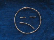 Sad face of twine in denim. Emoji sign handmade icon.  stock photography