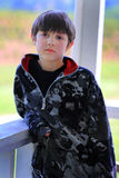 Sad Face Young Boy. Sad faced cute young boy with dark hair wearing a camo jacket leaning against a deck railing. Shallow depth of field in Royalty Free Stock Photos