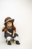 Sad faced girl doll sitting on a time out chair. Sad faced girl doll sitting on a time-out chair with blue brown and white clothing and hat with a bow. Tan wall royalty free stock images