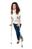 Sad faced woman limping with crutches Royalty Free Stock Image