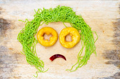 Sad faces on wood background made from vegetable and noodle with Stock Image