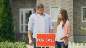 Sad family installing for sale signboard, have to sale their big house, crisis. Stock footage stock footage