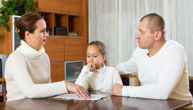 Sad family of three with documents Stock Photos