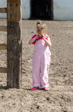 Sad farm girl. A sad little farm girl in pink overalls, cries outside the family barn Royalty Free Stock Photo