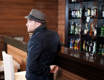 The sad fashionable young man in a bar Royalty Free Stock Photography
