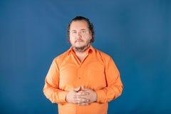 Sad fat man in orange shirt posing in the studio. Health problems. Sad fat man posing in the studio. Health problems. Excess weight royalty free stock photography
