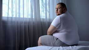 Sad fat man sitting on bed at home, looking at camera, depression, insecurities stock image