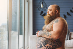 Sad fat man viewing street from apartment Stock Images