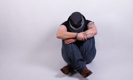 Sad and fearful person. Person with hat sitting and hiding royalty free stock photos