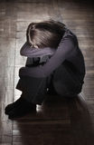 Sad feelings. Young girl sitting on the grungy  floor crying Royalty Free Stock Photos