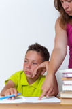 Sad female doing homework with her tween son royalty free stock photo