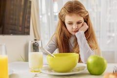 Sad female kid refuses healthy food Stock Photos