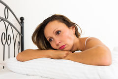 Sad female lies  in bed Royalty Free Stock Photo
