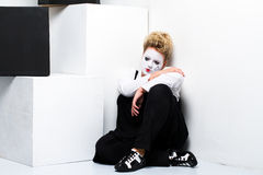 Sad female mime sitting on the floor Stock Photography