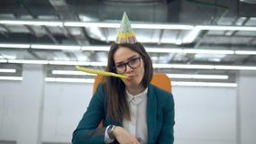 Sad female office worker in a festive hat is throwing confetti. 4K stock footage