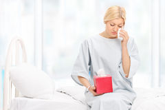 Sad female patient crying seated on a hospital bed. Sad woman in a hospital gown crying and wiping her tears seated on a hospital bed Stock Photo
