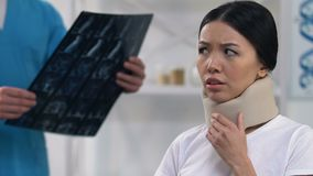 Sad female patient feeling uncomfortable in cervical collar, doctor examination. Stock footage stock footage