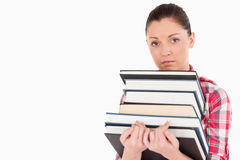 Sad female posing with books while standing Stock Photos