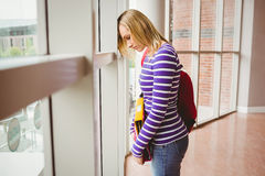 Sad female student by window in college Royalty Free Stock Images