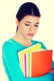 Sad female student with workbook. Stock Image