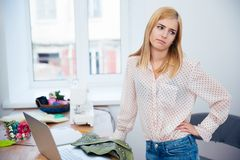 Sad female tailor standing in workshop Royalty Free Stock Photo