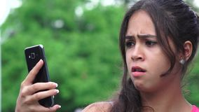 Sad female teen cellphone. A pretty young Colombian teen girl stock video footage