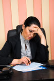 Sad financial consultant with problems. Sad  financial consultant woman with problems  looking over some  sales graphs and holding hand on forehead,check also Royalty Free Stock Images