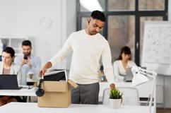 Sad fired office worker packing personal stuff stock photos
