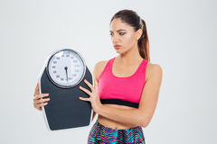 Sad fitness woman holding weighing machine royalty free stock photos