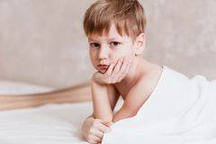 Sad five year old Caucasian boy covered with white Terry towel in bedroom after bathing. On white background stock photo